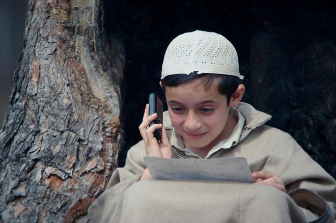 रेटिंग : 4 स्टार''द व्हाइट एलीफेंट'' और ''बाके की क्रेजी बारात'' जैसी फिल्मों के निर्देशक ऐजाज खान की तीसरी फिल्म''हामिद''एक सात वर्षीय बालक के नजरिए से कश्मीर घाटी में चल रहे खूनी संघर्ष, उथल पुथल, सीआरपीएफ जवानों पर पत्थर बाजी, लोगों के गुम होने आदि की कथा से ओतप्रोत आम बौलीवुड मसाला फिल्म नहीं है. अंतरराष्ट्रीय स्तर पर सराही जा चुकी फिल्म ''हामिद'' मूलतः अमीन भट्ट लिखित कश्मीरी नाटक''फोन नंबर 786'' पर आधारित है. जिसमें मासूम हामिद अपने भोलेपन के साथ ही अल्लाह व चमत्कार में यकीन करता है. मासूम हामिद जिस भोलेपन से अल्लाह व कश्मीर के मुद्दों को लेकर सवाल करता है, वह सवाल विचलित करते हैं. वह कश्मीर में चल रहे संघर्ष की पृष्ठभूमि में बचपन की मासूमियत और विश्वास की उपचार शक्ति का ''हामिद'' में बेहतरीन चित्रण है. मासूम हामिद उस पवित्रता का प्रतीक बनकर उभरता है, जो भय और मृत्यु के बीच एक आशा की किरण है.फिल्म की कहानी शुरू होती है एक कारखाने से, जहां रहमत (सुमित कौल) और रसूल चाचा (बशीर लोन) नाव बनाने में मग्न है. जब रात होने लगती है, तो रसूल चाचा, रहमत को घर जाने के लिए कहते हैं. रास्ते में रहमत को सीआरपीएफ के जवानों के सवालों के जवाब देने पड़ते हैं. इधर घर पर रहमत के लाडले सात साल के बेटे हामिद को अपने पिता के आने का इंतजार है. क्योंकि उसे मैच देखना है और टीवी चलाने के लिए बैटरी की जरुरत है. जब रहमत अपने घर पहुंचता है, तो रहमत का बेटा हामिद (ताल्हा अरशद) जिद करता है कि उसे मैच देखना है, इसलिए अभी बैटरी लेकर आएं. रहमत की पत्नी और हामिद की मां इशरत (रसिका दुग्गल) के मना करने के बावजूद रहमत अपने बेटे की मांग को पूरा करने के लिए रात में ही बैटरी लेने निकल जाता है, पर वह घर नहीं लौटता. उसके बाद पूरे एक वर्ष बाद कहानी शुरू होती है. जब इशरत अपने बेटे की अनदेखी करते हुए अपने पति की तलाश में भटक रही है. वह हर दिन पुलिस स्टेशन जाती रहती है. इधर हामिद की जिंदगी भी बदल चुकी है. एक दिन उसके दोस्त से ही उसे पता चलता है कि उसके अब्बू यानी कि पिता अल्लाह के पास गए हैं. तब वह अपने अब्बू के अल्लाह के पास से वापस लाने के लिए जुगत लगाने लगता है. एक दिन एक मौलवी से उसे पता चलता है कि अल्लाह का नंबर 786 है. तो वह 786 को अपनी बाल बुद्धि के बल पर दस नंबर में परिवर्तित कर अल्लाह को फोन लगाता है.